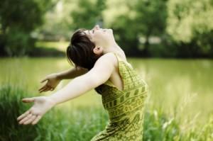 Chica con los brazos extendidos disfrutando del sol