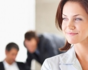 An attractive young business woman looking away with colleagues working behind