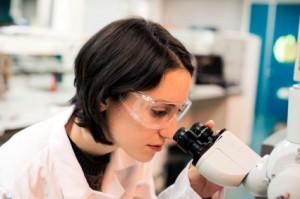 rol de científico, una mujer con máscara mira por un microscopio